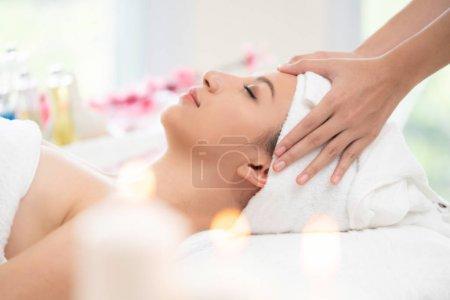 Photo pour Détendue femme allongée sur le lit de la spa pour le traitement de spa massage du visage et la tête par massothérapeute dans une station thermale de luxe. Bien-être, stress relief et rajeunissement concept. - image libre de droit