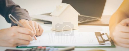 Photo for Client signs document regarding real estate activity next to lawyer or real estate agent sitting at office desk. Business concept of selling and buying house. - Royalty Free Image