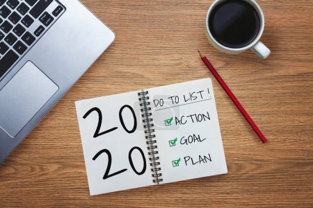 Photo for New Year Resolution Goal List 2020 - Business office desk with notebook written in handwriting about plan listing of new year goals and resolutions setting. Change and determination concept. - Royalty Free Image